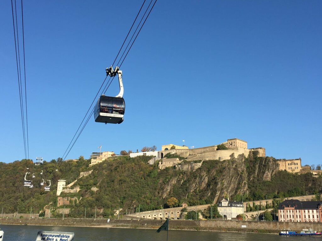 black cable car over green trees and buildings during daytime